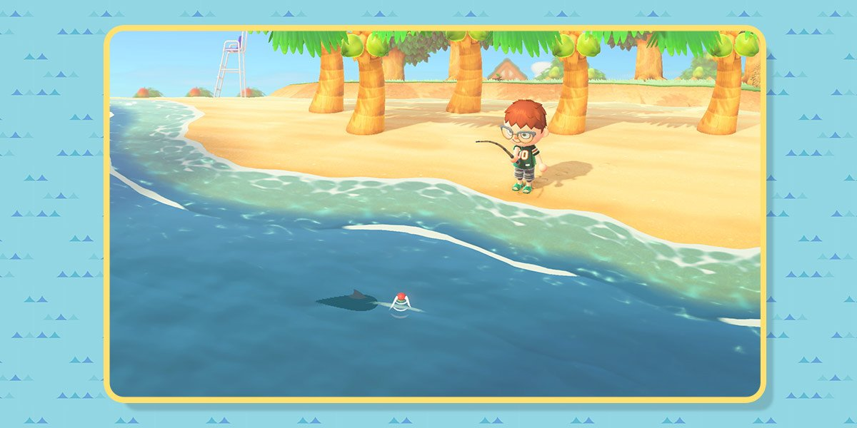 The player stands on the beach, fishing from the ocean shore. Their line is in the water. A fish shadow with a fin swims near the red bobbin.